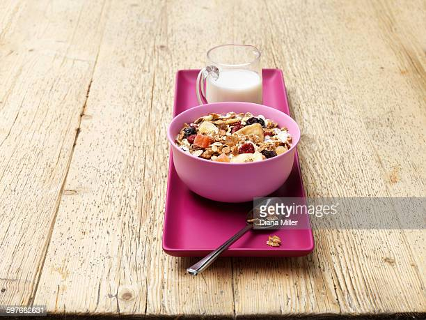 Breakfast bowl of muesli with fruit and milk on wood