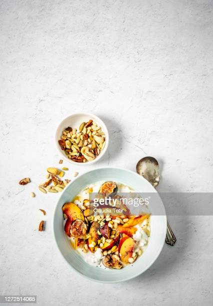 breakfast bowl: yogurt with fruit (peaches and figs), nuts and seeds on white background - granola stock pictures, royalty-free photos & images