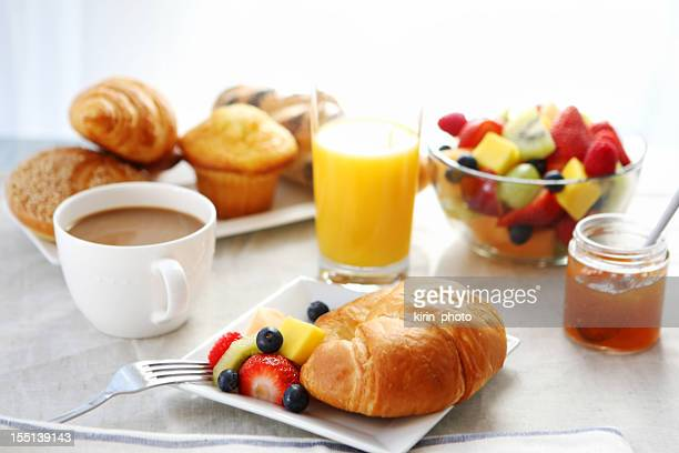 Petit déjeuner, un croissant, une salade de fruits et du café