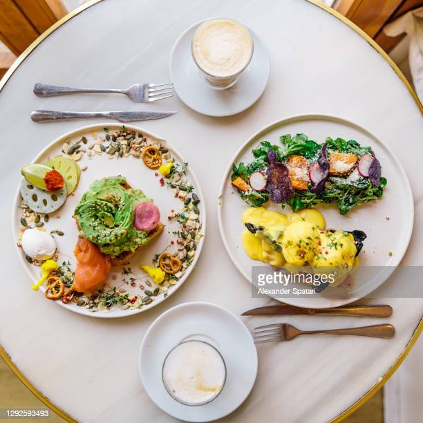 breakfast for two persons with avocado toast and eggs benedict on waffle, directly above view - romance stock pictures, royalty-free photos & images
