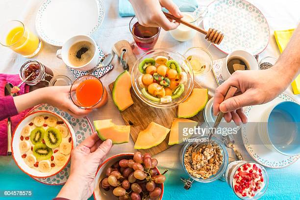 Breakfast, laid table, fresh muesli, hands taking