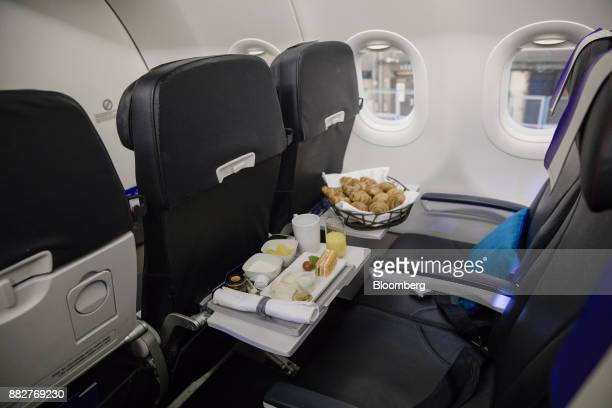 A breakfast meal and a basket of croissants sit on business class seating foldout tables on board a Joon passenger jet the new lowcost carrier...