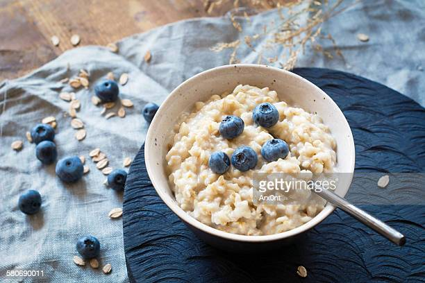 breakfast oats, porridge with blueberries - rolled oats stock photos and pictures