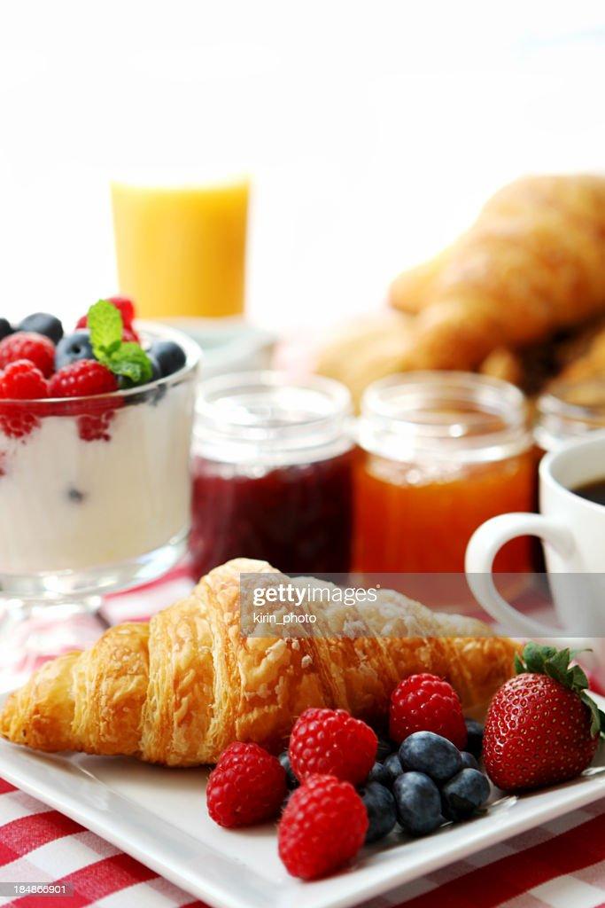 Breakfast of fruit, juice, yogurt, croissant and coffee : Stock Photo