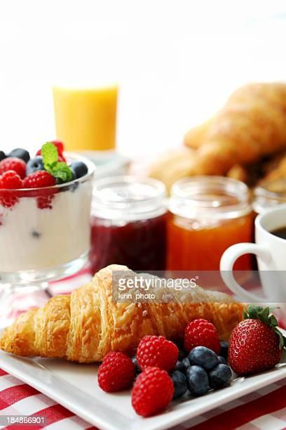 Breakfast of fruit, juice, yogurt, croissant and coffee
