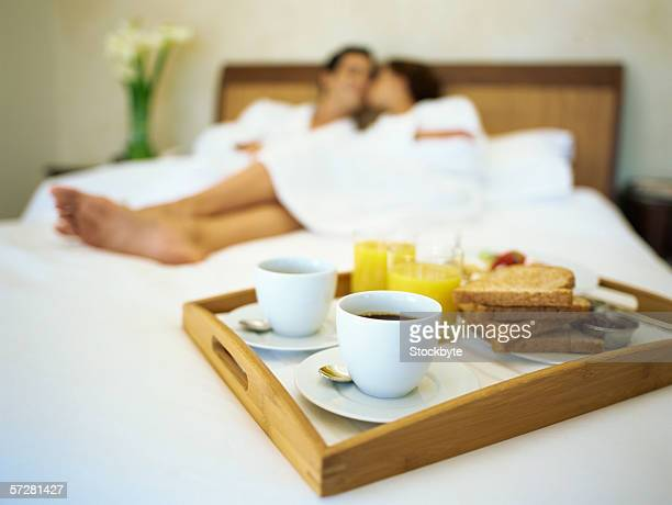Breakfast on a bed with a young couple lying on bed in the background