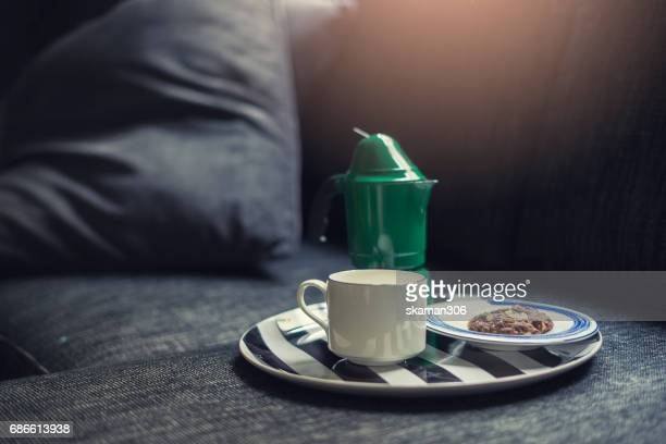 breakfast on bed with coffee pot with cookie on modern sofa near window