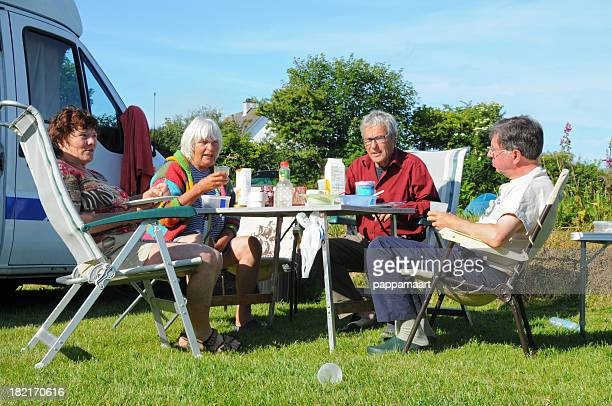 Breakfast on campsite with four seniors and motor home