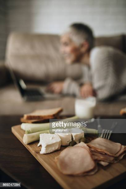 breakfast on cutting board with woman in the background. - baloney stock photos and pictures