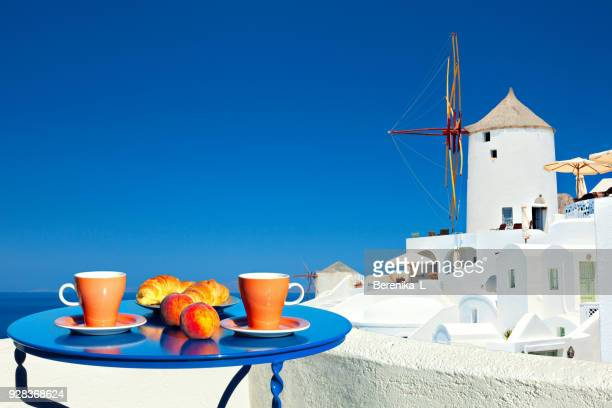 Breakfast on the terrace on the background of the classic Santorini view.