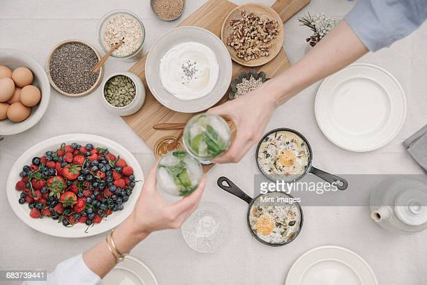 Breakfast. Overhead view of dishes of fruit, berries and yoghurt, eggs and cooked omelettes. Two people reaching to dish out food.