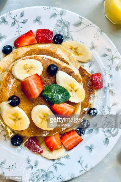 breakfast pancakes with banana, strawberries and blueberries - pancake day stock pictures, royalty-free photos & images