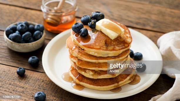 breakfast pancakes with blueberries, butter and honey - american culture stock pictures, royalty-free photos & images