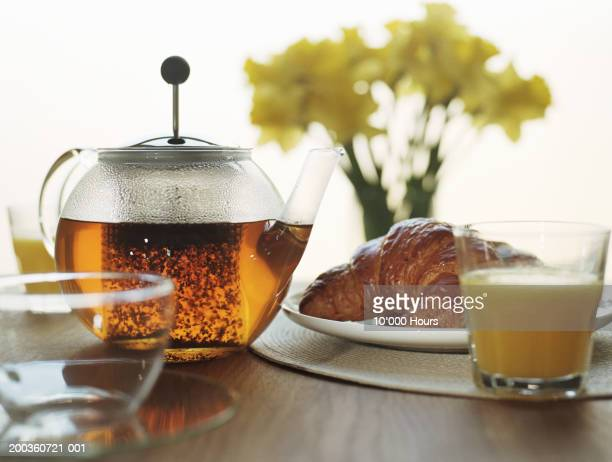 Breakfast place setting, with tea, orange juice and croissant,close-up