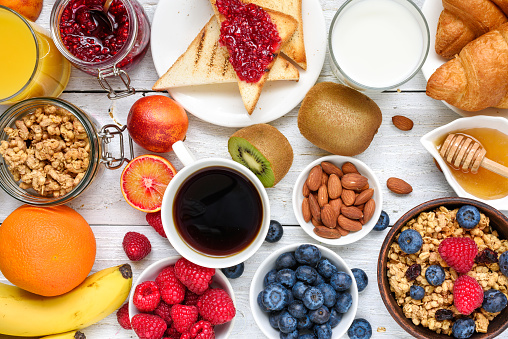 Breakfast served with coffee, orange juice, toasts, croissants, cereals, milk, nuts and fruits. Balanced diet 935702416