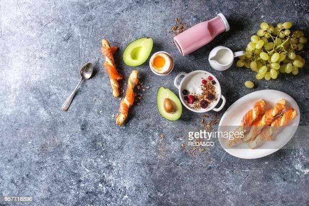 Breakfast set with smoked salmon on crispy breadsticks yogurt smoothie avocado muesli milk berries and green grape over blue texture background Top...