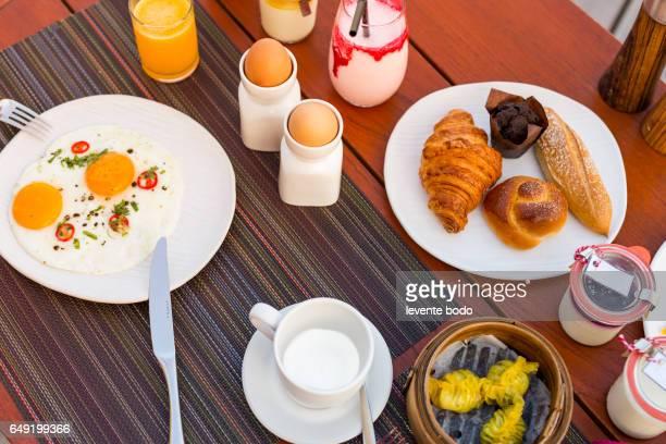 Breakfast table eggs croissant fresh homemade jam fruit milkshake. Top view.