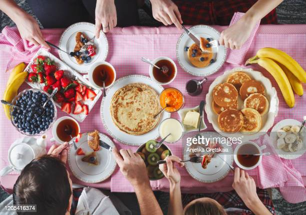 breakfast table. flat lay of eating peoples hands over breakfast table with crepes, pancakes, tea and berries. - butter stock pictures, royalty-free photos & images
