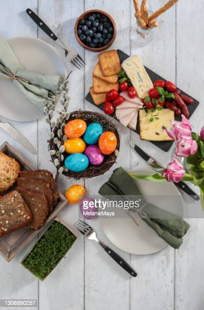 breakfast table for easter sunday celebration with colorful eggs and charcuterie - easter dinner stock pictures, royalty-free photos & images