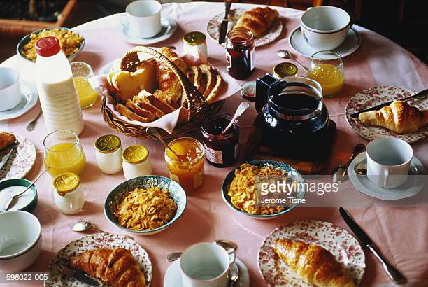 Breakfast table including bowls of cereal and croissants