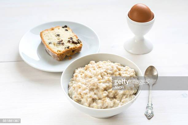 breakfast table set: porridge, cake and boiled egg - rolled oats stock photos and pictures