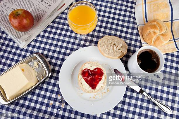 A breakfast table with a bread roll with heart shaped jam on it