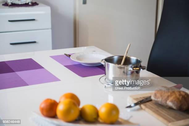 breakfast table with a pot, bread, soup plate and orange fruit - wohnraum bildbanksfoton och bilder