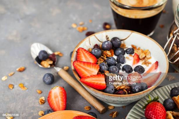 breakfast table with cereal granola, fresh berries and coffee - nut food stock photos and pictures