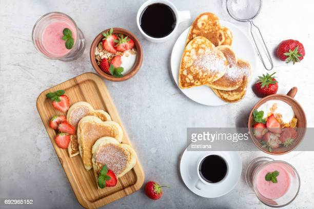 Breakfast table with heart shaped pancakes, strawberries, muesli, fruit smoothies and coffee