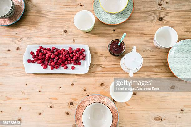Breakfast table with raspberries and jam