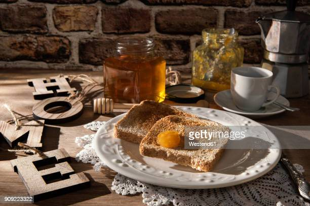 Breakfast table with toast, orange marmalade, honey and espresso