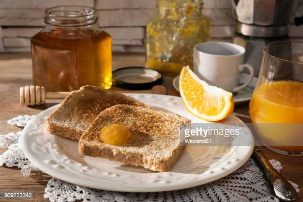 Breakfast table with toast, orange marmalade, honey, orange juice and espresso