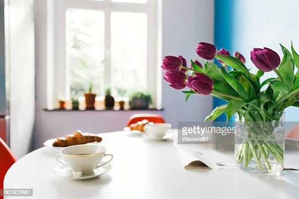 Breakfast table with tulips, croissants and cups of coffee