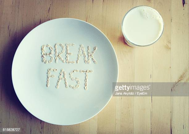 Breakfast Text On White Plate With Glass Of Milk Served On Table