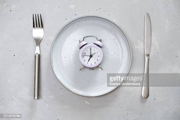 breakfast time concept with alarm clock plate, fork, knife, spoon, - fasting activity stock pictures, royalty-free photos & images