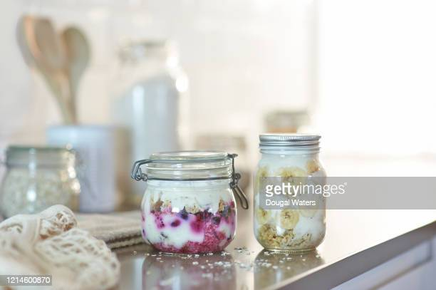 breakfast to go jars of granola, dairy free yogurt with berries or bananas. - {{asset.href}} stock pictures, royalty-free photos & images