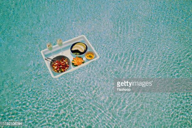 a breakfast tray floats across a pool (wide) - lugar turístico fotografías e imágenes de stock