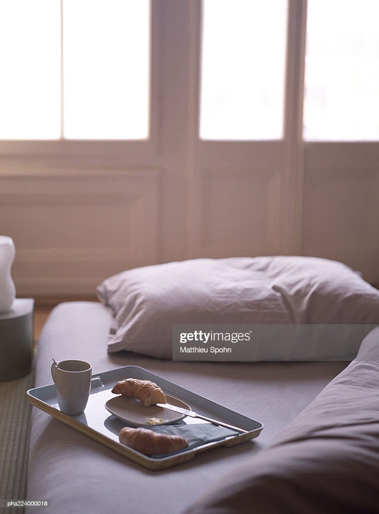 Breakfast tray sitting on bed. : Stockfoto