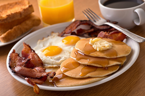 Breakfast with bacon, eggs, pancakes, and toast 533645537