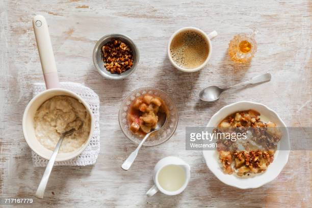 Breakfast with bowl of porridge with rhubarb compote, honey and nuts and cup of coffee