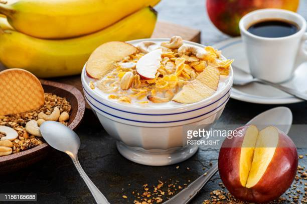 Breakfast with cornflakes and granola with slice of apple fruit