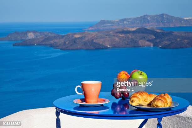 breakfast with croissants and fresh fruit at early morning served on the balcony with sea volcanic view. - aegean sea stock pictures, royalty-free photos & images