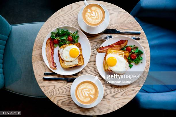 breakfast with croque madame and coffee served for two people in a cafe, high angle view - restaurant stock pictures, royalty-free photos & images