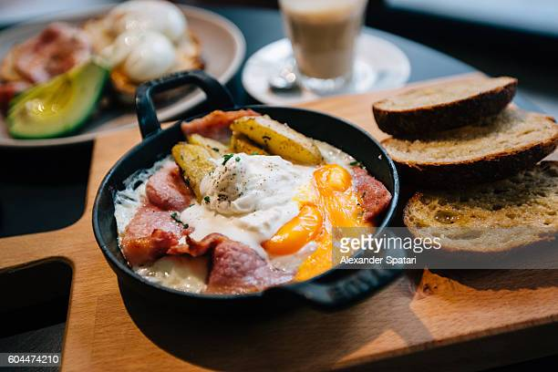 Breakfast with eggs, bacon and potatoes served in the skillet