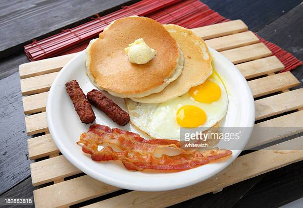 A breakfast with pancakes eggs and bacon on white plate