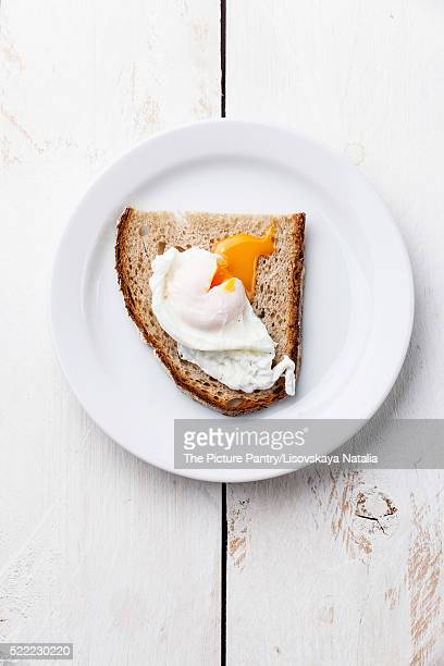 Breakfast with poached egg and bread on white wooden background