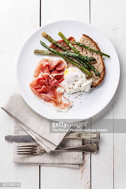 Breakfast with poached egg, parma and asparagus on white wooden