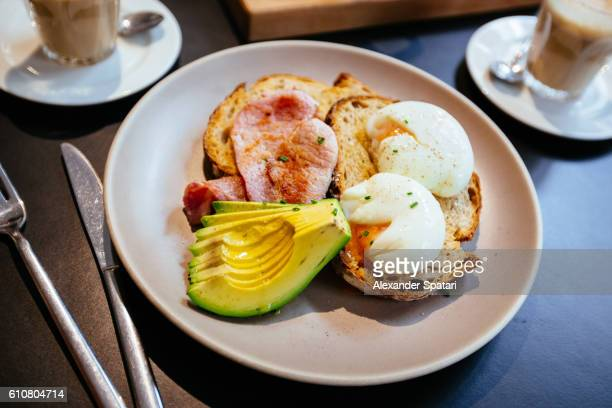 Breakfast with poached eggs, fresh avocado and bacon served on toasted bread