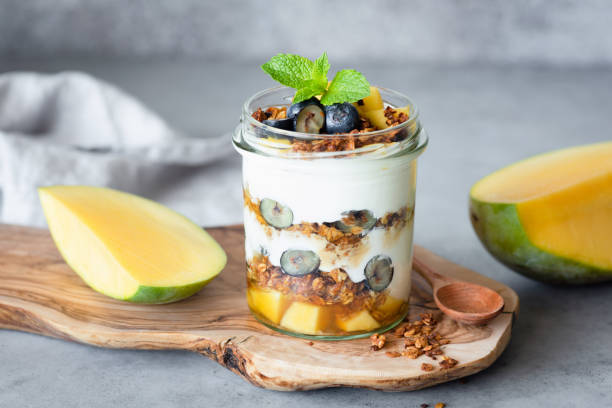 breakfast yogurt parfait with granola, mango, berries in jar - 餐後甜品 個照片及圖片檔