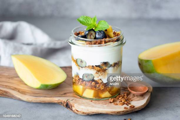 breakfast yogurt parfait with granola, mango, berries in jar - dessert stock pictures, royalty-free photos & images